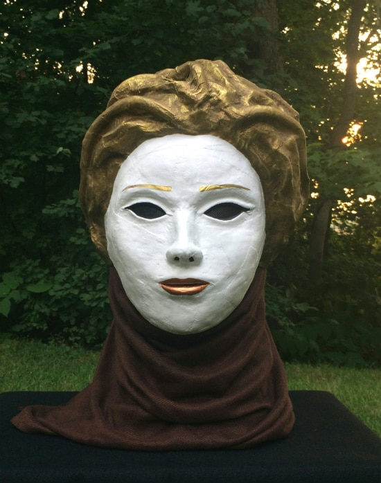 Front of mask that looks like woman's face. It is painted pure white, with golden hair and copper lips. Green leafy background with rays of setting sun.