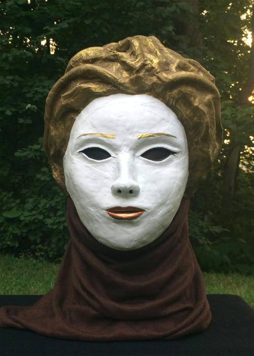 Mask that looks like woman's face painted pure white with golden hair.