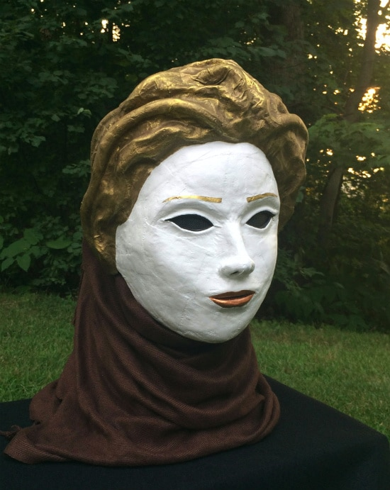 "Right angle view. The mask, which is on (and concealing) a manikin head, is ""wearing"" a dark brown scarf."